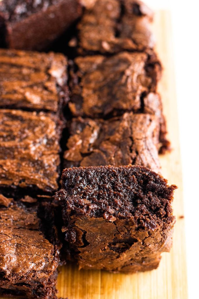 stack of three fudgy brownies with salted caramel sauce on top