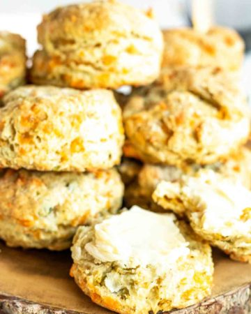 a pile of biscuits on a wood board with one open and buttered