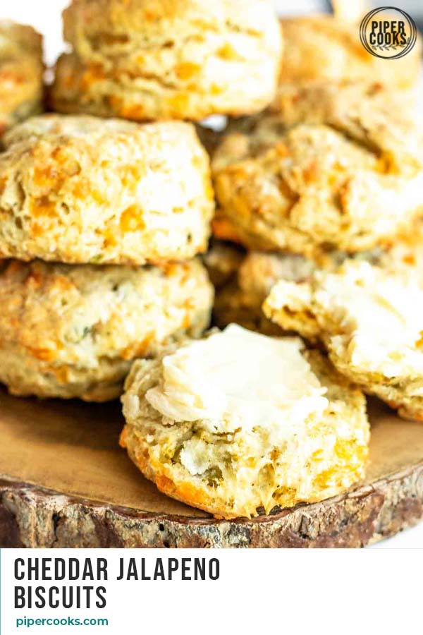 a pile of biscuits on a wood board with one open and buttered and text overlay for pinterest