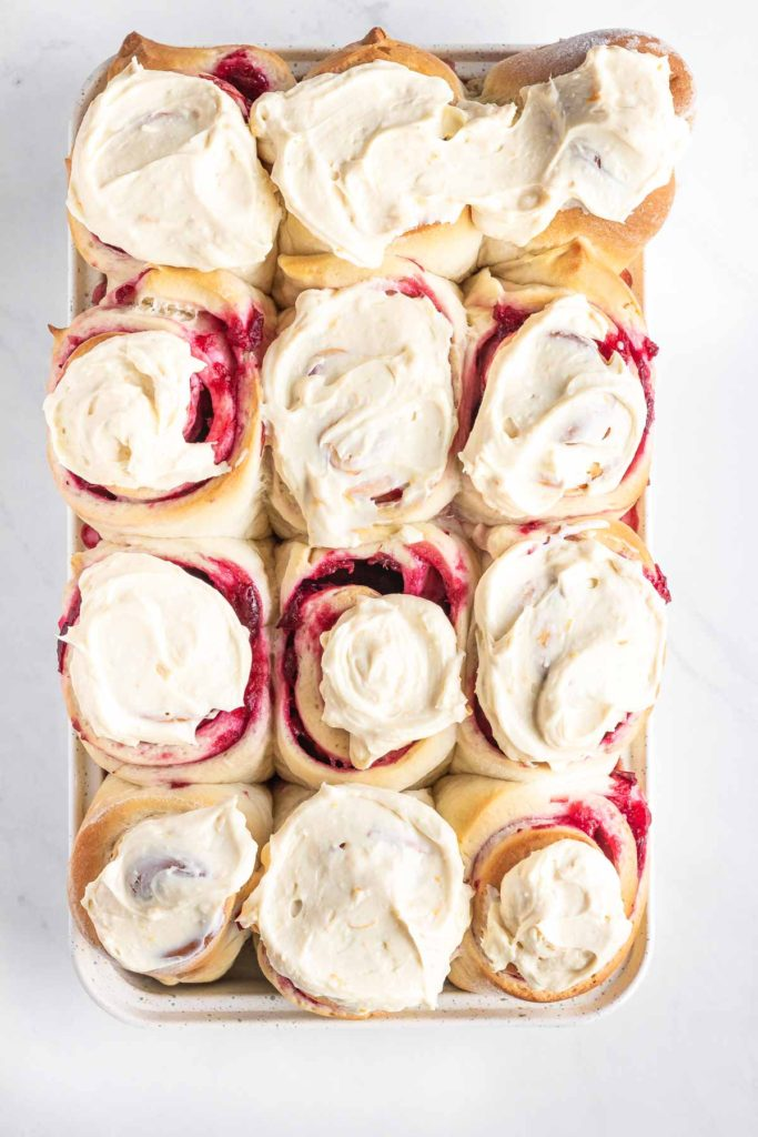 12 iced cranberry sweet rolls in a pan
