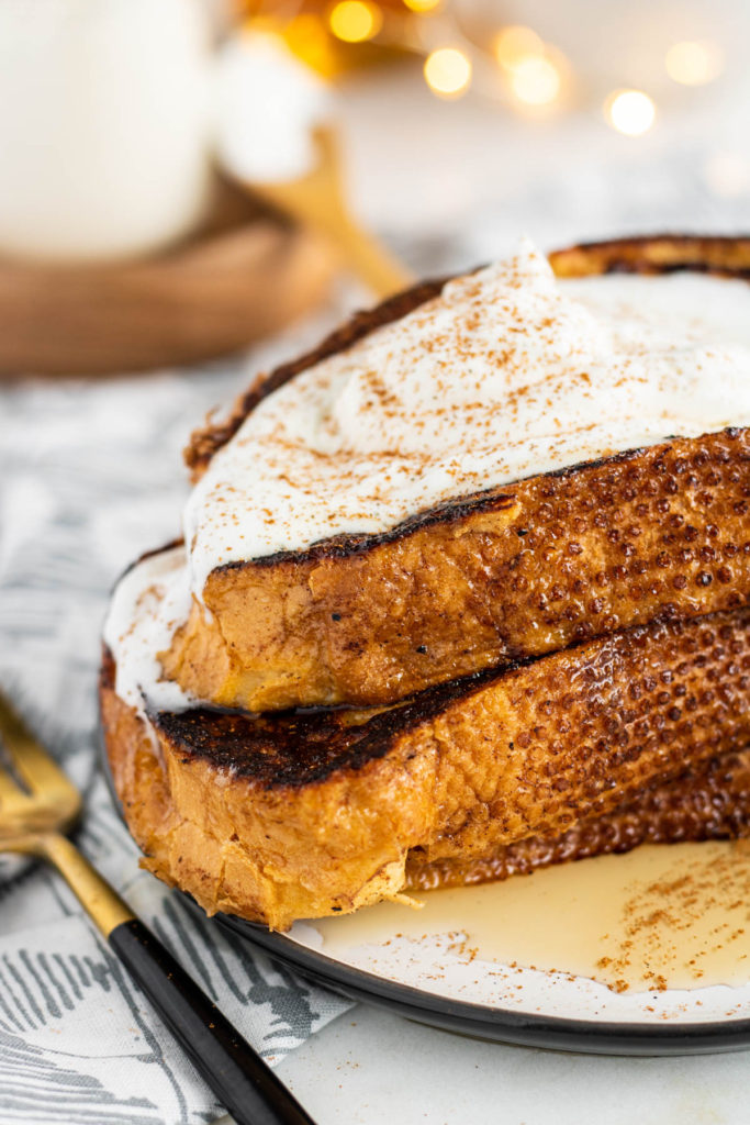 eggnog french toast on a plate with syrup, whipped cream and sprinkle of nutmeg
