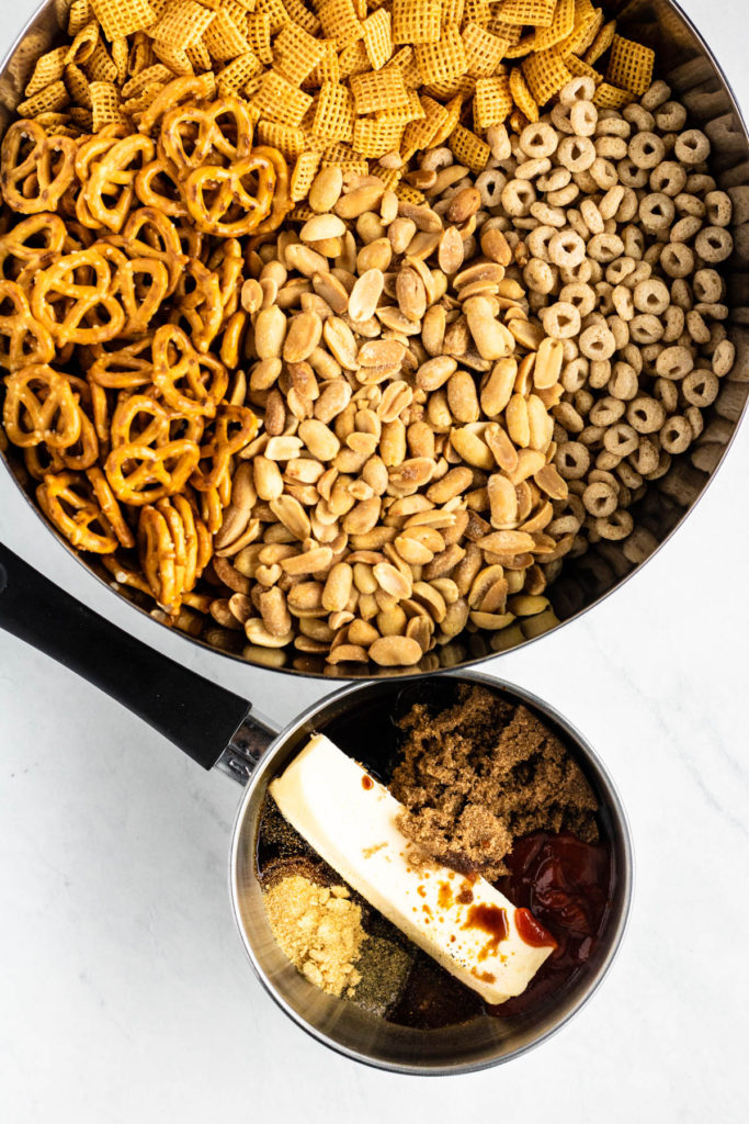 chex mix in a bowl with glaze ingredients in a pot beside