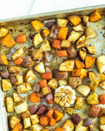 cubed potatoes on a sheet pan with garlic