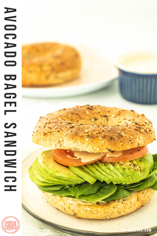 toasted bagel sandwich with tomato, avocado and spinach with a text overlay for Pinterest