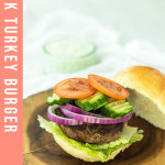 Greek turkey burger on a wood platter with text overlay for pinterest