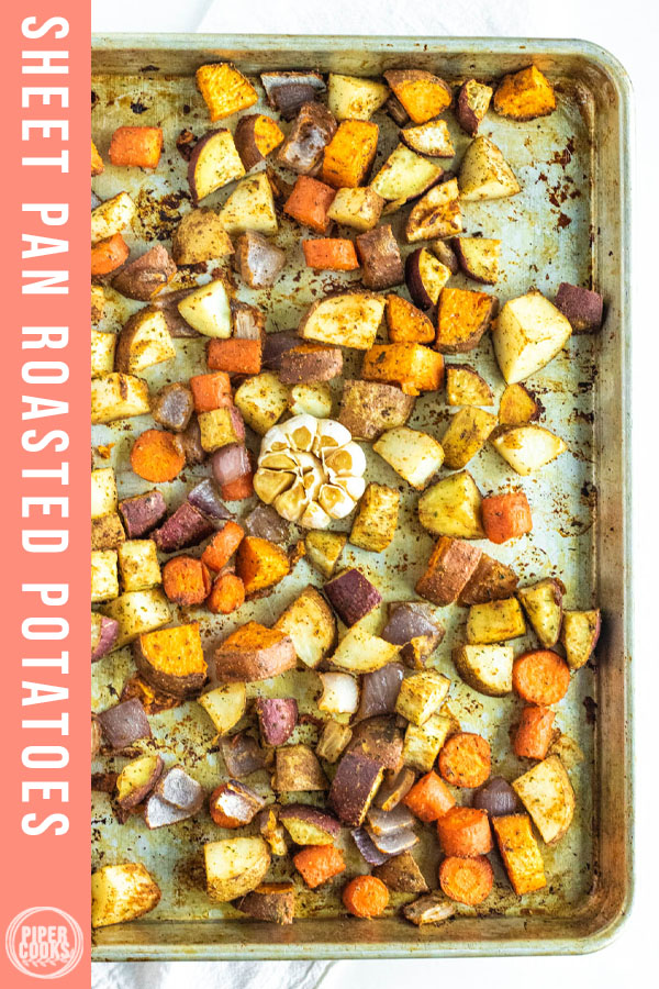 cubed potatoes on a sheet pan with garlic with text overlay for pinterest