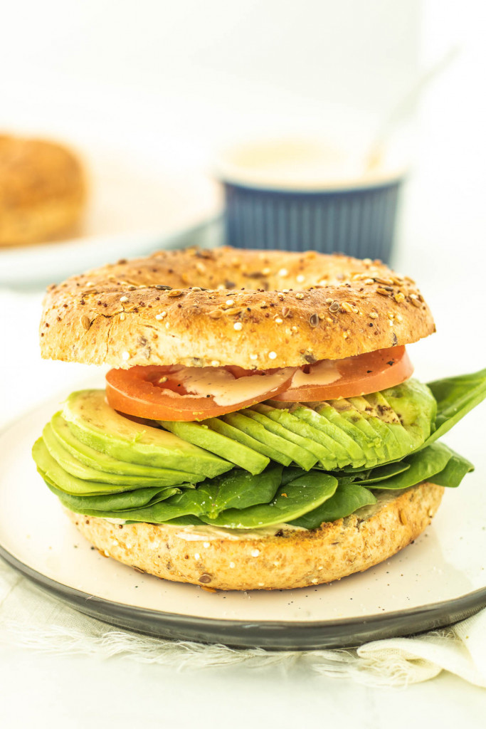 toasted bagel sandwich with tomato, avocado and spinach