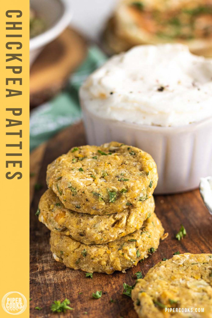 stacked chickpea patties on a wooden platter with a text overlay for Pinterest