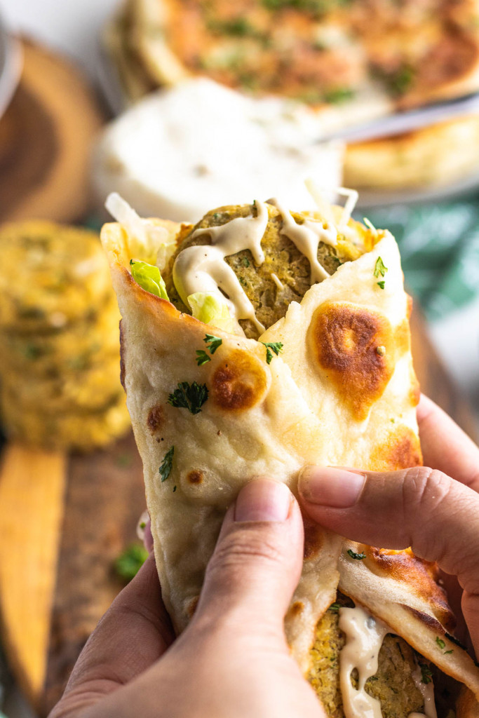 hands holding a flatbread wrapped with chickpea patties inside