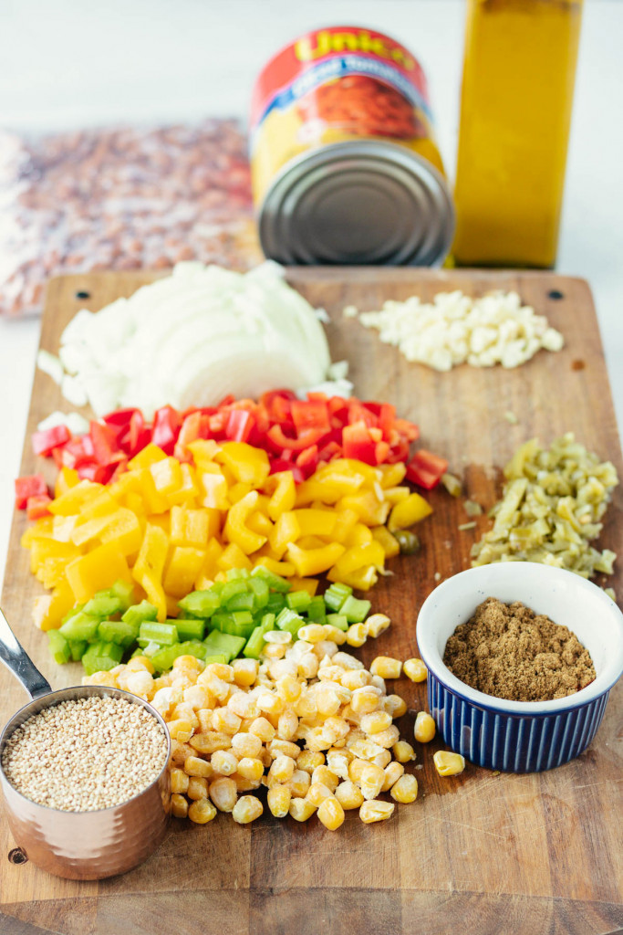 ingredients on a chopping board - bell peppers, corn, onion, quinoa, spices