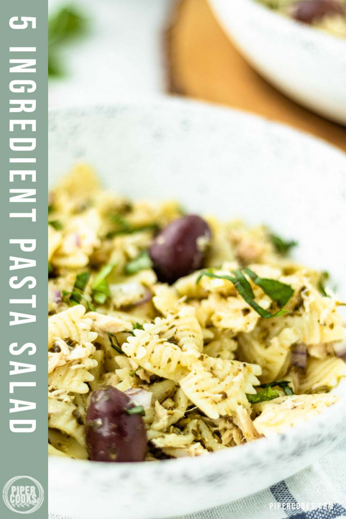 pasta salad in a bowl with olives on top and a text overlay for Pinterest