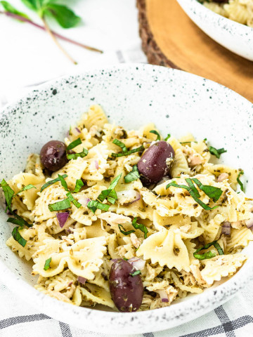 pasta salad in a bowl with olives on top