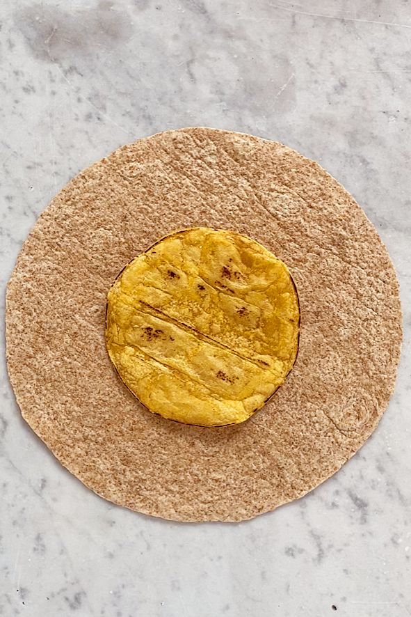 corn tortilla on a large flour tortilla