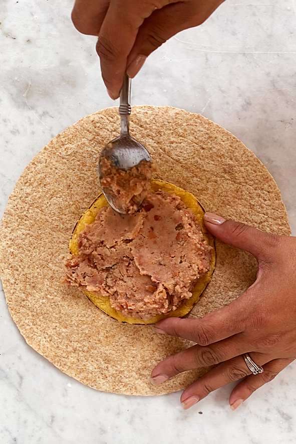 spreading refried beans on a corn tortilla