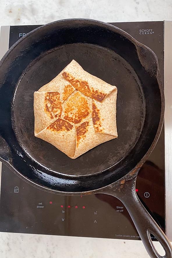 frying a breakfast crunchwrap in a cast iron pan