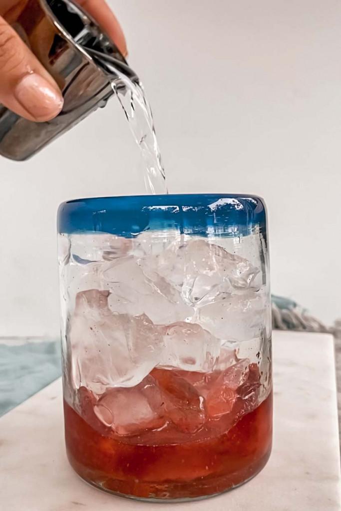 adding vodka to cocktail glass.
