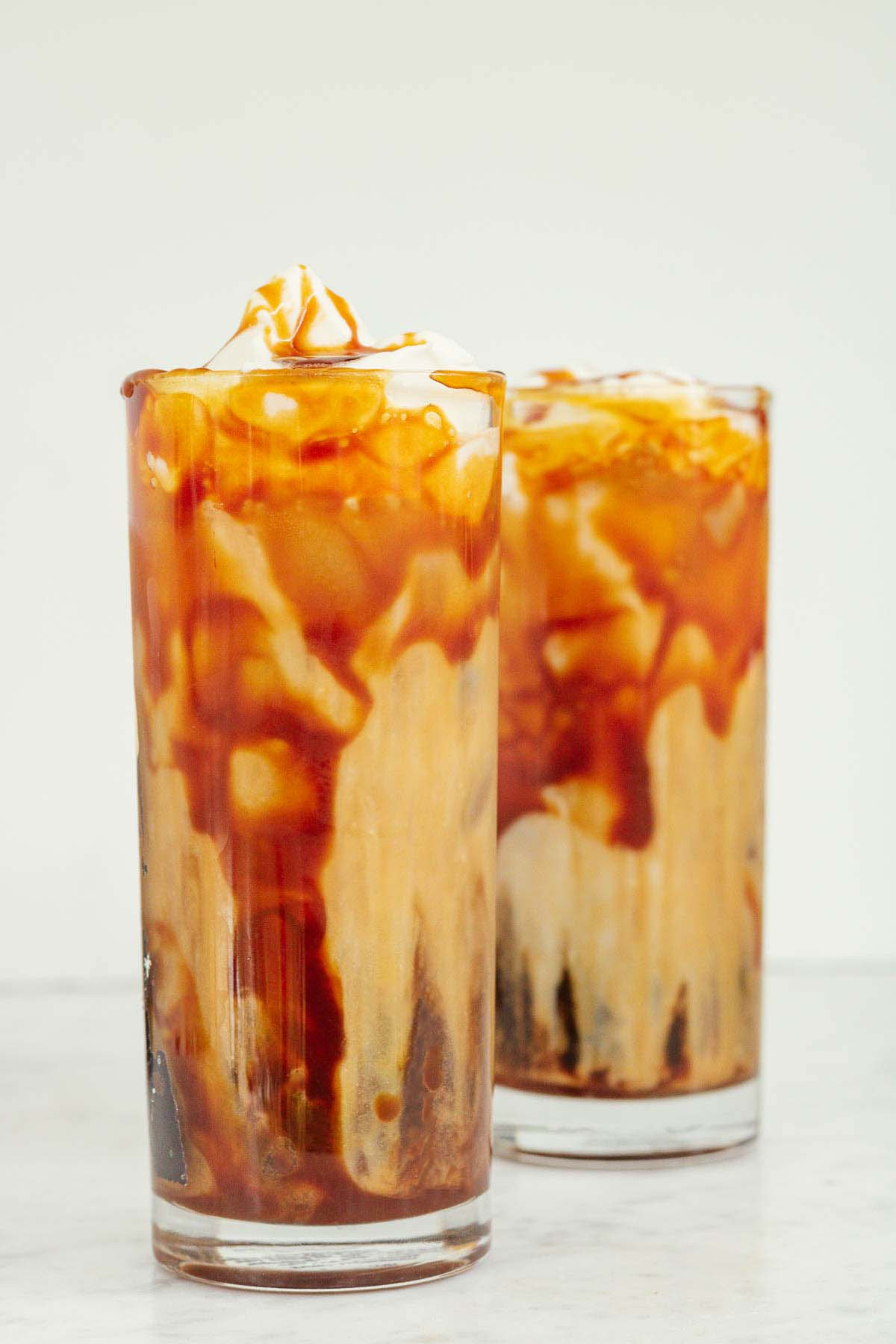 iced caramel latte with whipped cream and caramel sauce on top