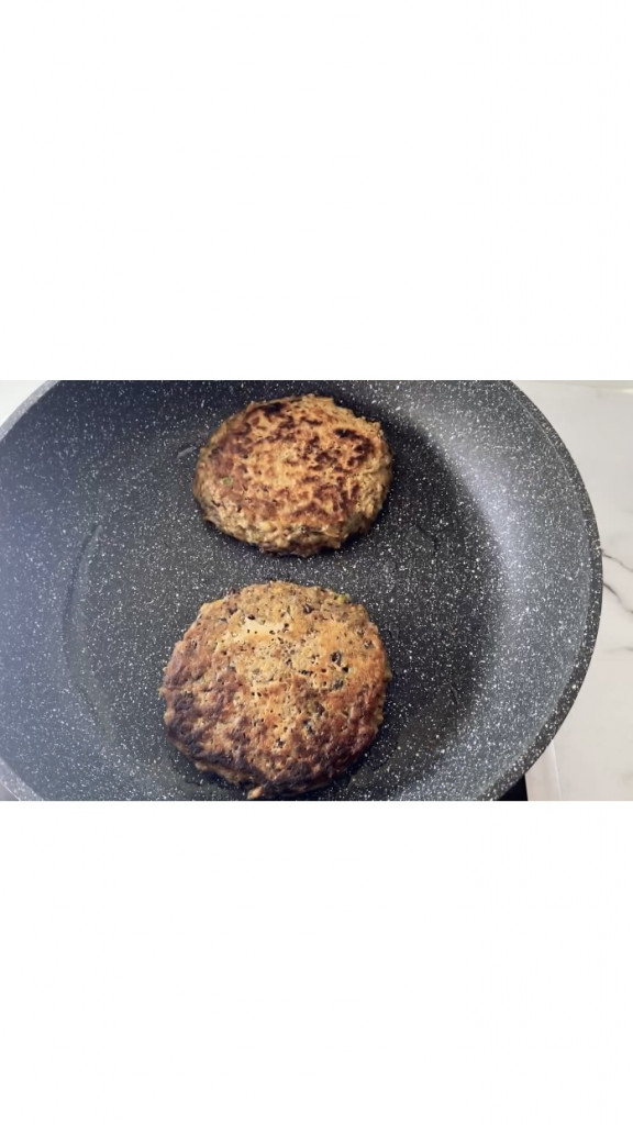 cooking the second side of black bean burgers in a frying pan