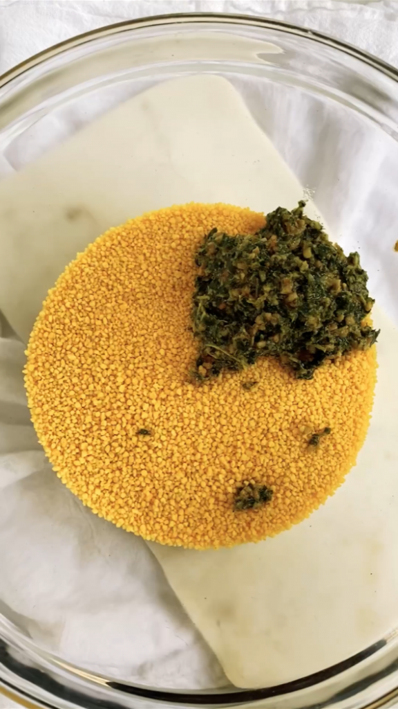 adding pesto to dry couscous